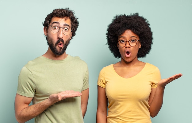 Casal de amigos multirraciais parecendo surpresos e chocados, com o queixo caído segurando um objeto com a mão aberta na lateral