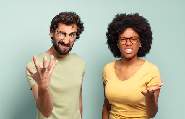 Casal de amigos multirraciais parecendo zangados, irritados e frustrados gritando o que há de errado com você