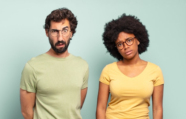 Casal de amigos multirraciais se sentindo perplexo e confuso, com uma expressão muda e atordoada olhando para algo inesperado