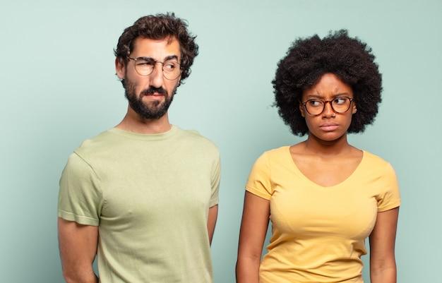 Casal de amigos multirraciais se sentindo triste, chateado ou com raiva e olhando para o lado com uma atitude negativa, franzindo a testa em desacordo