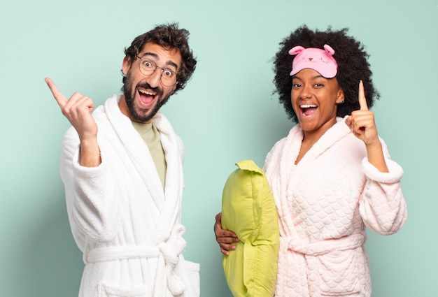 Casal de amigos multirraciais se sentindo um gênio feliz e animado depois de realizar uma ideia, levantando o dedo alegremente, eureka !.