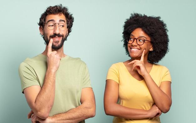 Casal de amigos multirraciais sorrindo alegremente e sonhando acordado ou duvidando