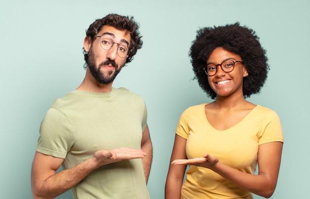 Casal de amigos multirraciais sorrindo alegremente, se sentindo feliz e mostrando um conceito no espaço da cópia com a palma da mão