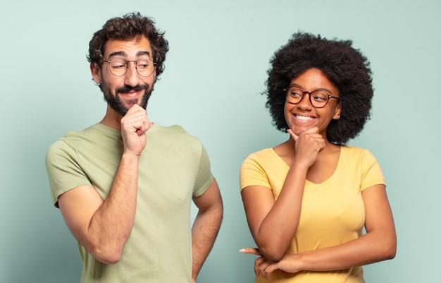 Casal de amigos multirraciais sorrindo com uma expressão feliz e confiante com a mão no queixo, pensando e olhando para o lado