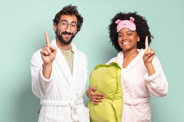 Casal de amigos multirraciais sorrindo e parecendo amigáveis, mostrando o número um ou o primeiro com a mão para a frente, em contagem regressiva.