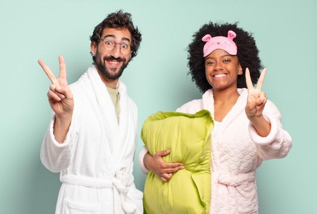Casal de amigos multirraciais sorrindo e parecendo felizes, despreocupados e positivos, gesticulando vitória ou paz com uma mão. pijama e conceito de casa