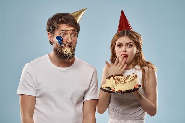 Casal de aniversário com um bolo e uma vela usando chapéus de festa isolado
