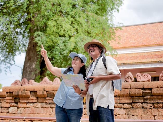 Casal de aposentados andando pela cidade com um mapa. conceito de viajante de verão.