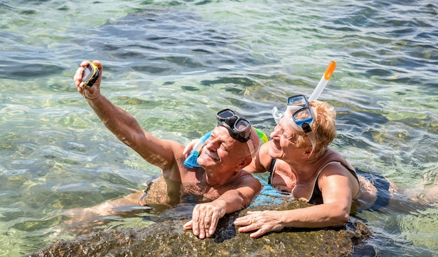 Casal de aposentados feliz tomando selfie em excursão no mar tropical com câmera de água e máscara de snorkel