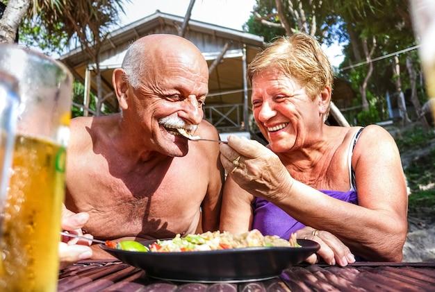 Casal de aposentados se divertindo comendo comida local em restaurante tailandês com bar na praia ao ar livre