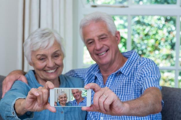 Casal de aposentados tomando selfie a sorrir