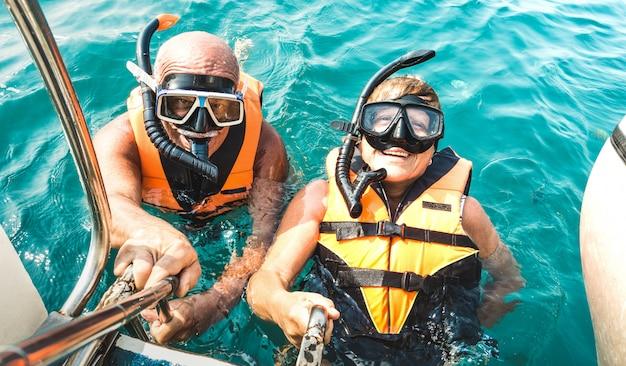 Casal de aposentados tomando selfie feliz em excursão no mar tropical com coletes salva-vidas e máscaras de snorkel