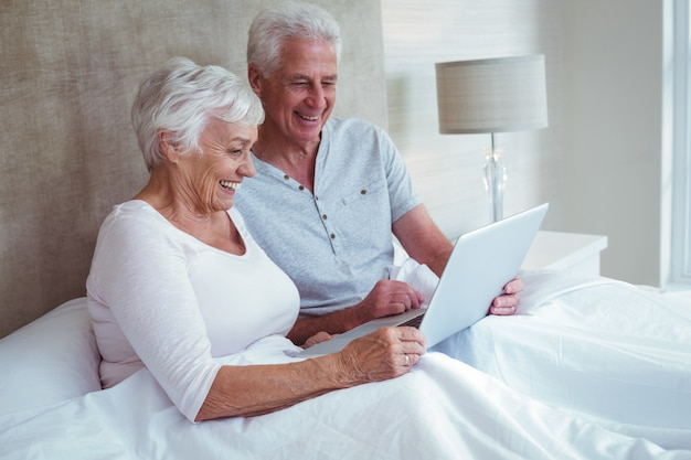 Casal de aposentados usando laptop enquanto está sentado na cama