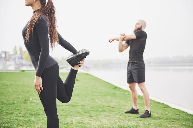 Casal de aptidão alongamento ao ar livre no parque perto da água. jovem barbudo homem e mulher exercitando juntos de manhã