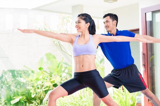 Casal de aptidão asiática no treino de esporte em casa tropical