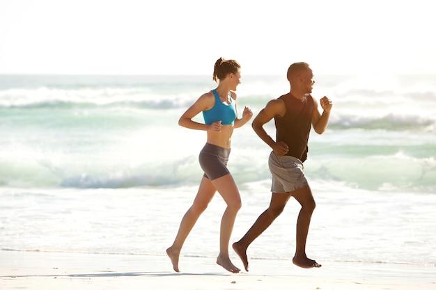 Casal de aptidão correndo ao longo do mar na praia