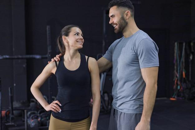 Casal de atleta se divertindo após o treino. mulher sorridente, falando com um amigo no ginásio.