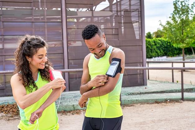 Casal de atletas conectando seus fones de ouvido ao smartphone que carregam nos braços
