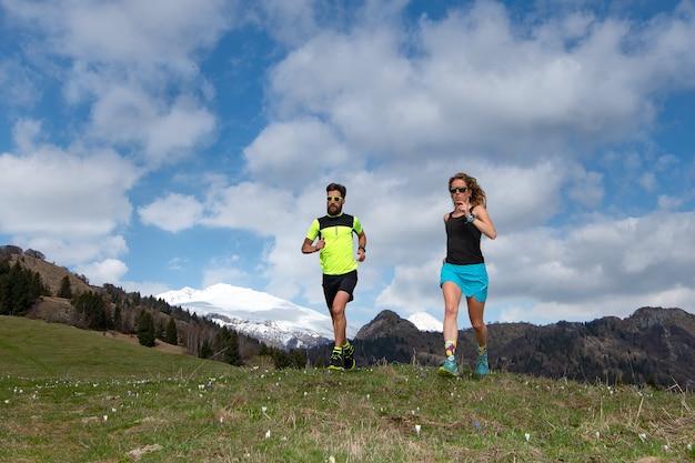Casal de atletas masculinos e femininos treina nas montanhas