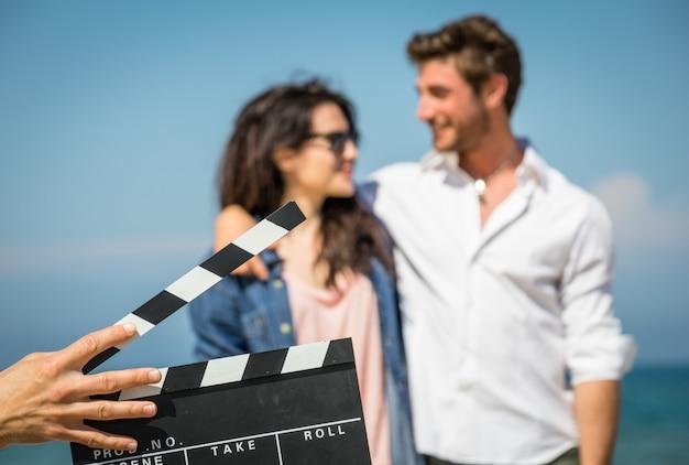 Casal de atores na praia. operador de câmara segura a ripa