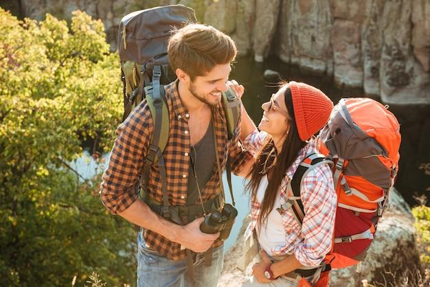 Casal de aventureiros se olhando nos olhos perto do cânion