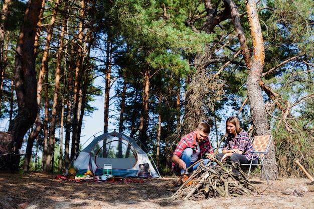 Casal de baixo ângulo com barraca de acampamento durante a noite