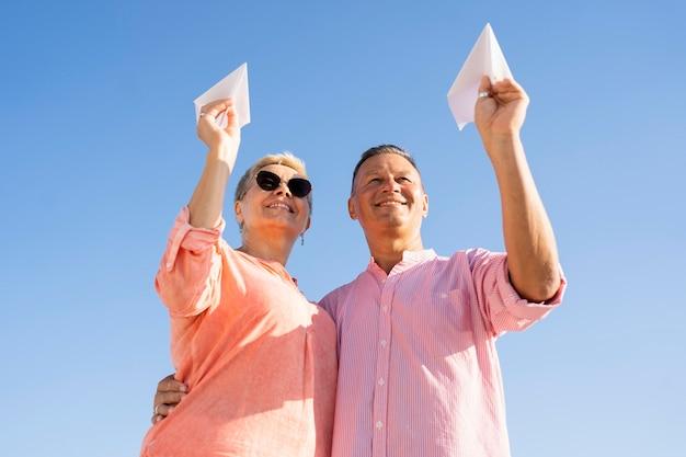 Casal de baixo ângulo segurando aviões de papel