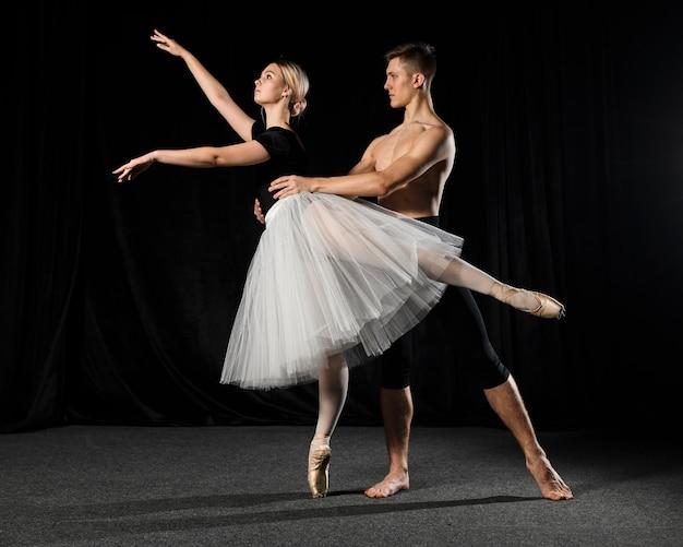 Casal de balé posando de tutu e calças justas