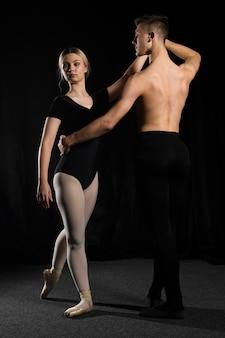 Casal de balé posando em collant e calças justas