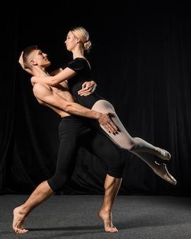 Casal de balé posando enquanto abraçava