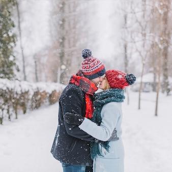 Casal de beijo surpreendente na neve caindo