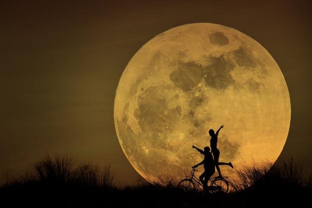 Casal de bicicleta no luar
