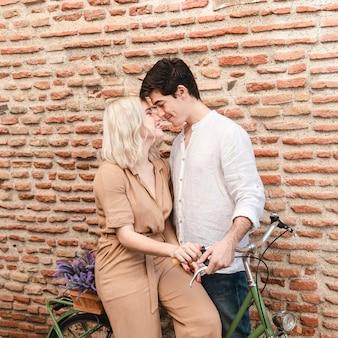 Casal de bicicleta posando enquanto inclinando-se para um beijo