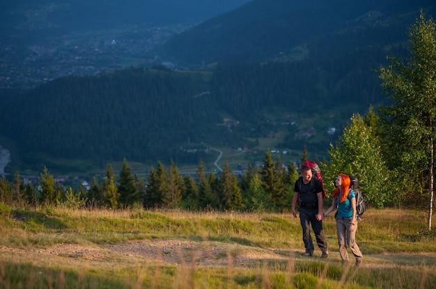 Casal de caminhantes com mochilas andando na área de belas montanhas