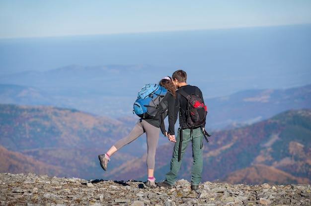 Casal de caminhantes com mochilas no cume da montanha