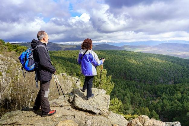 Casal de caminhantes contemplando a paisagem do topo da montanha