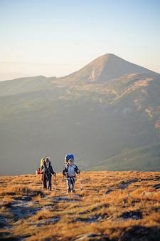 Casal de caminhantes nas montanhas dos cárpatos com mochilas