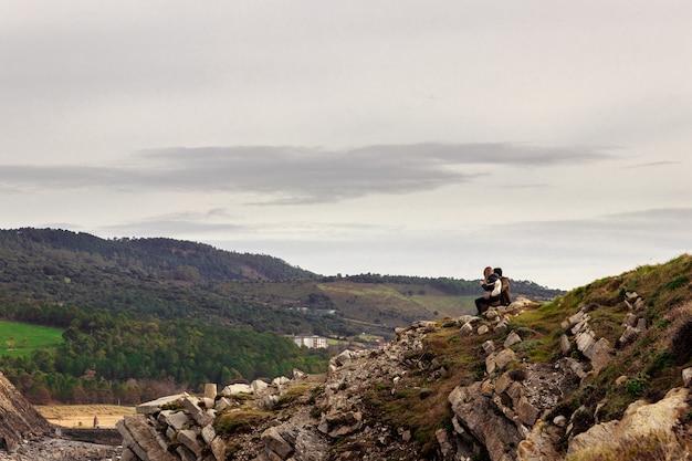 Casal de caminhantes românticos aventureiros sentado nas rochas e olhando para as montanhas