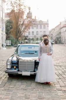 Casal de casamento de luxo feliz beijando e abraçando perto de carro retrô preto no antigo centro da cidade, edifícios antigos no fundo.