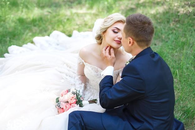 Casal de casamento emocional na grama verde na primavera. amor de duas pessoas. noiva e noivo gentil abraçando e beijando no dia do casamento na natureza. retrato de recém-casados bonitos ao ar livre. conceito de casamento