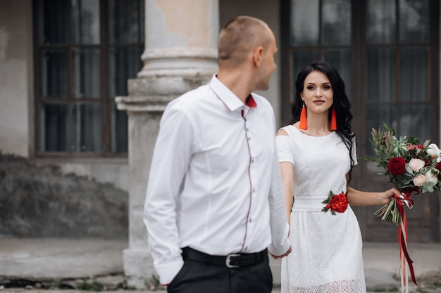 Casal de casamento encantador e elegante coloca antes de um edifício de um antigo castelo
