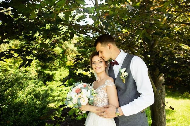 Casal de casamento incrível posando em um fundo verde natural