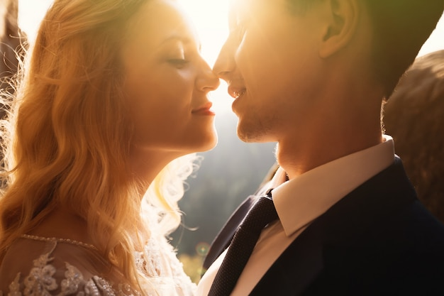Casal de casamento romântico conto de fadas beijando ao pôr do sol