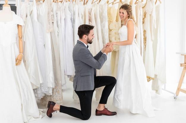 Casal de caucasiano, noivo coloca um anel de casamento.