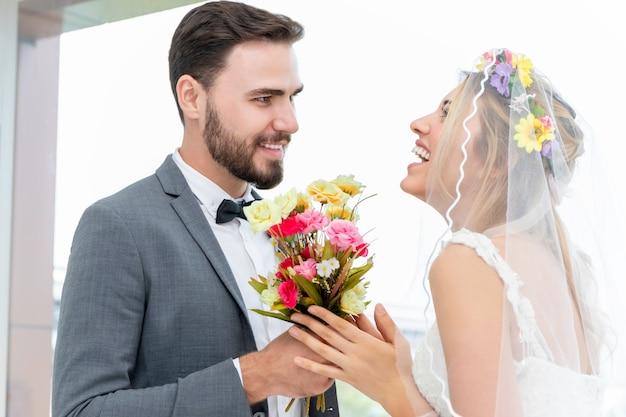 Casal de caucasiano, noivo dá noiva atual no estúdio de casamento.
