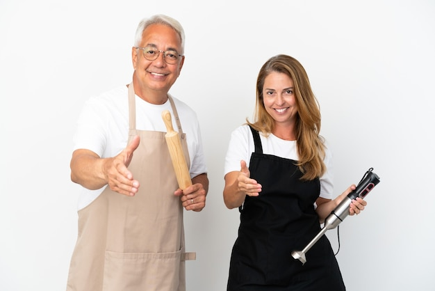 Casal de chefs de meia-idade isolado em fundo branco apertando as mãos para fechar um bom negócio