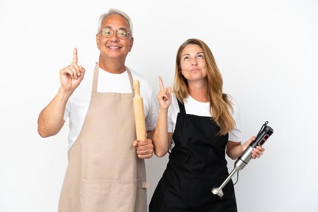 Casal de chefs de meia-idade isolado em fundo branco, mostrando e levantando um dedo em sinal dos melhores