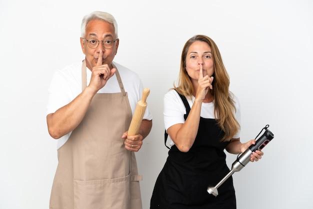 Casal de chefs de meia-idade isolado em fundo branco mostrando sinal de silêncio gesto colocando o dedo na boca