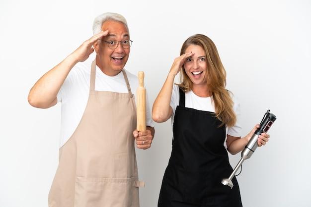 Casal de chefs de meia-idade isolado em um fundo branco acaba de perceber algo e tem a intenção de encontrar a solução