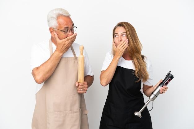 Casal de chefs de meia-idade isolado em um fundo branco cobrindo a boca com as mãos por dizer algo impróprio